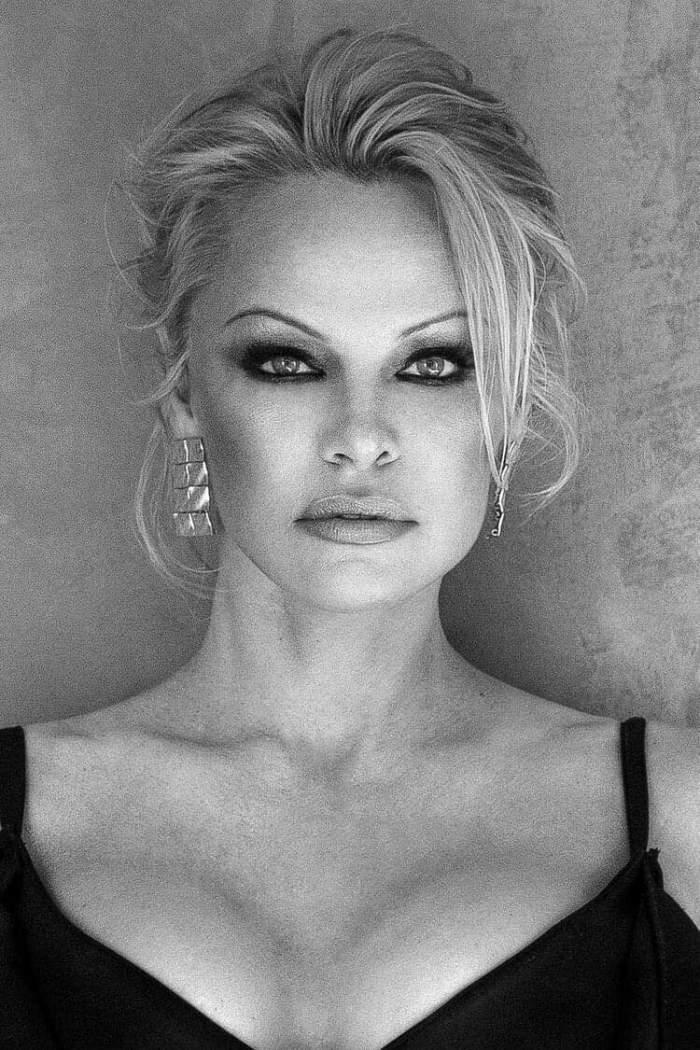 Pamela Anderson poartă o rochie neagră cu decolteu. Vedeta are părul prins în coc.