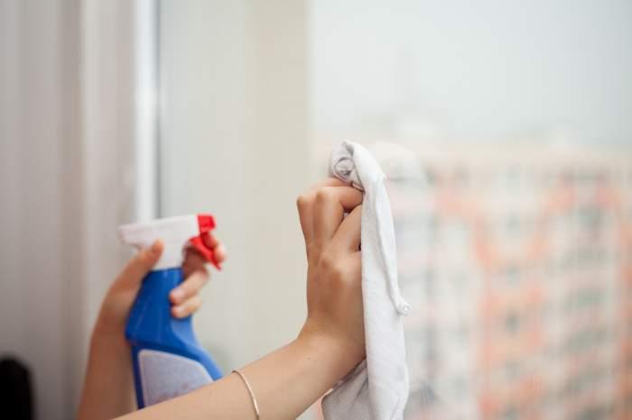 Imagine ilustrativa cu o femeie care spala un geam cu un produs din comert