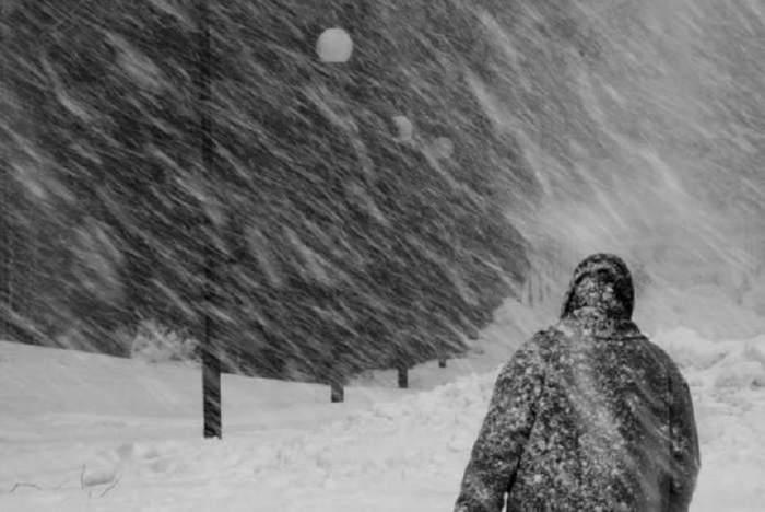 O persoană îmbrăcată în negru, de iarnă, merge prrin viscol și zăpadă