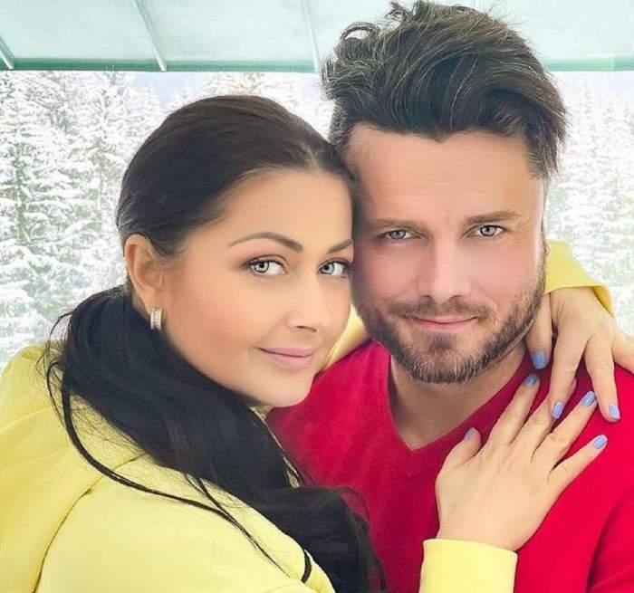 Gabriela Cristea și Tavi Clonda se țin în brațe. Ea poartă un hanorac galben și are părul prins în coadă, iar el o bluză roșie.