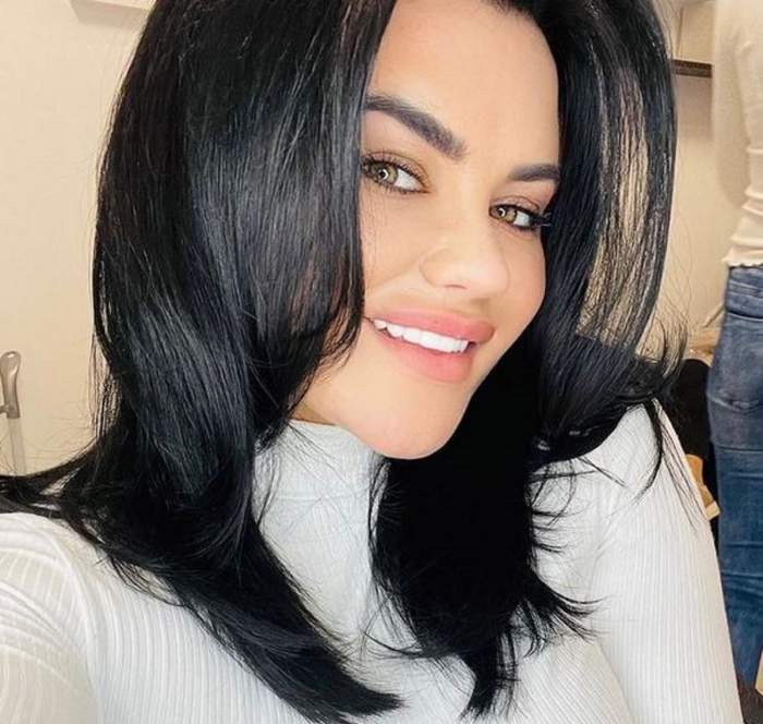 Carmen de la Sălciua își face un selfie. Artista poartă o bluză albă și zâmbește larg.
