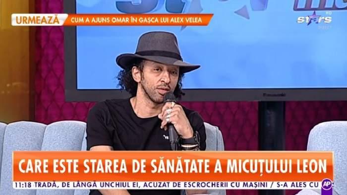 Kamara se află pe canapeaua de la Star Matinal. Artistul vorbește la microfon și poartă o pălărie gri pe cap. Cântărețul e îmbrăcat cu un tricou negru.