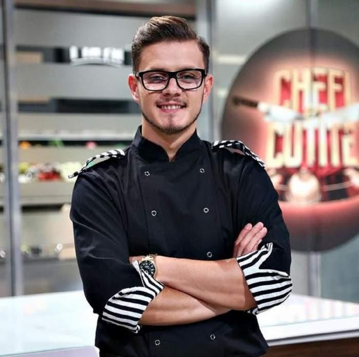 Ionuț Belei este la Chefi la cuțite. Tânărul poartă uniformă neagră de bucătare și își ține mâinile în sân.