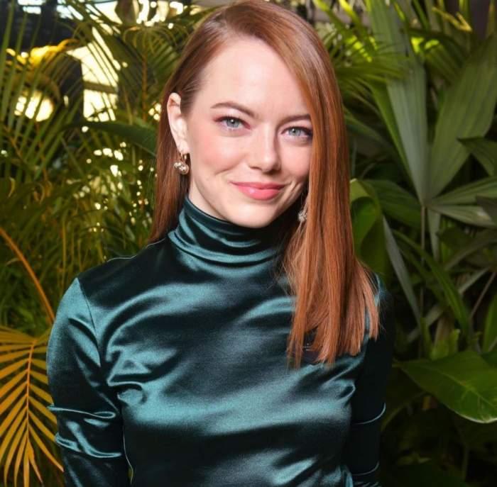Emma Stone este la un eveniment, poarta o rochie din satin verde, are parul desprins