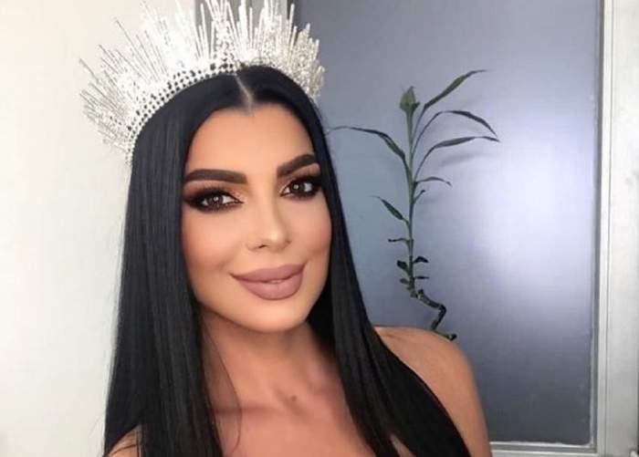 Andreea Tonciu poartă o coroniță arginite pe cap. În spatele vedetei se vede o plantă în ghiveci.