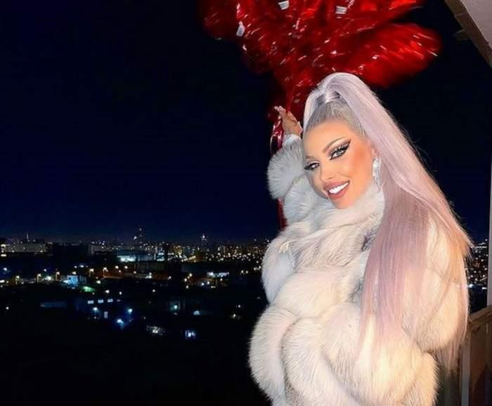 Loredana Chviu poartă o haină de iarnă albă. Vedeta ține în mâini niște baloane roșii.