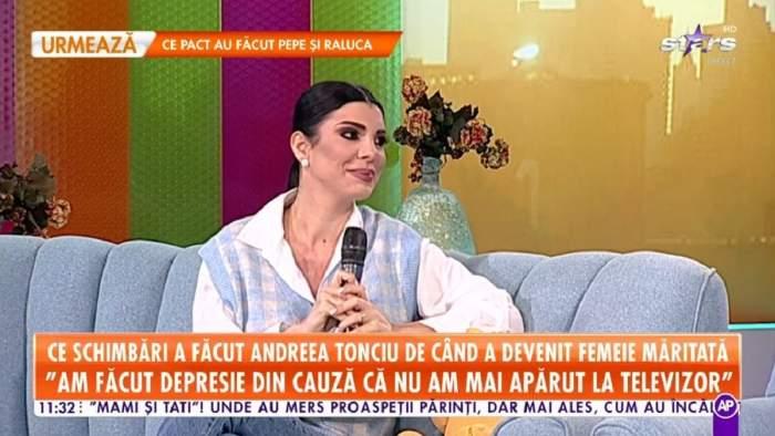 Andreea Tonciu se află pe canapeaua de la Star Matinal. Vedeta poartă o cămașă albă și un pulover albastru, în partea de jos niște blugi.