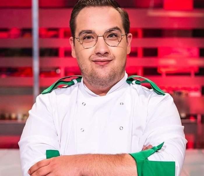 Răzvan Babană este la Chefi la cuțite. Fostul concurent ține mâinile în sân și poartă uniformă de bucătar albă, cu mâneci și umeri verzi.