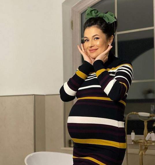 Olguța Berbec poartă o rochie neagră, cu dungi albe și galbene. Vedeta se află în baie și i se vede burtica de gravidă.