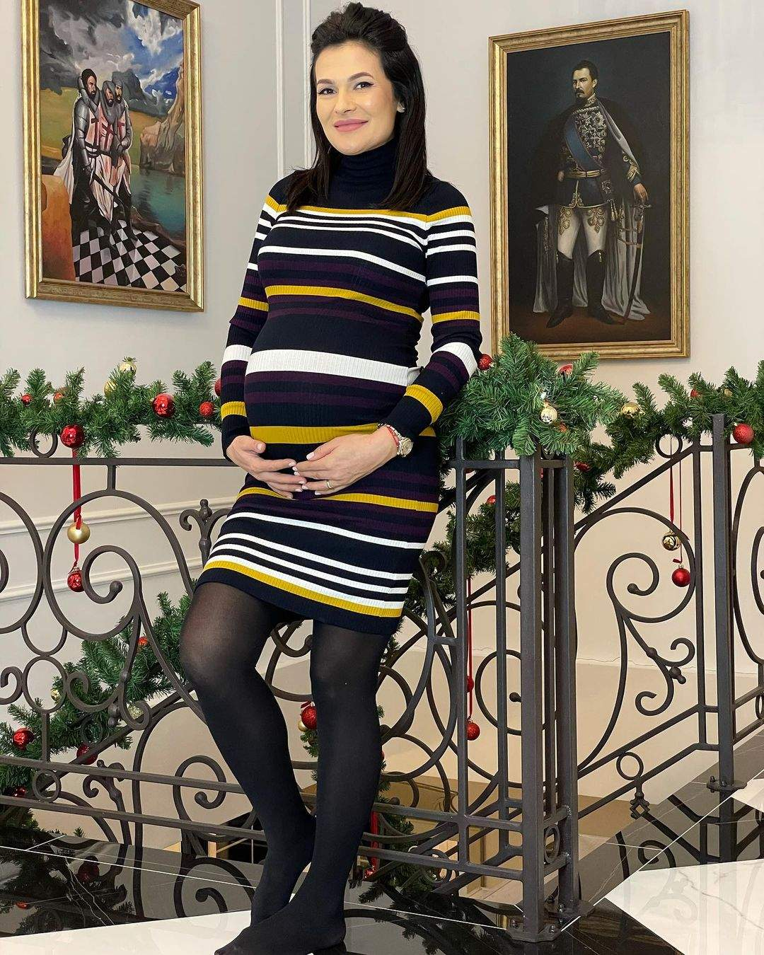 Olguța Berbec poartă o rochie neagră, cu dungi albe și galbene. Vedeta se află în fața unor scări și își ține mâinile pe burtica de gravidă.