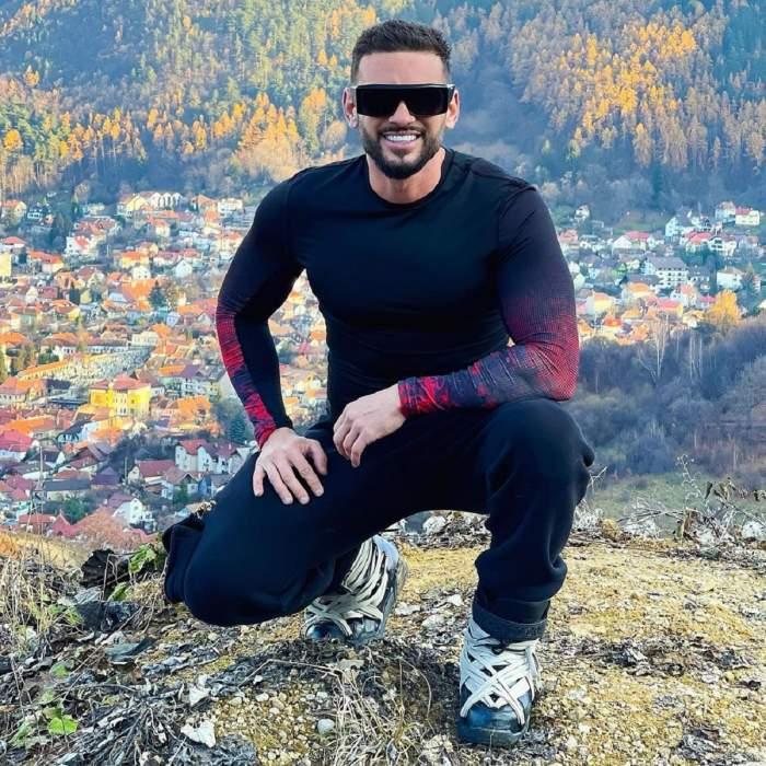 Dorian Popa e îmbrăcat cu o pereche de pantaloni negri și o bluză neagră, cu mâneci roșii. Artistul poartă o pereche de ochelari, iar în spatele lui se văd mai multe case. Acesta stă pe vine.
