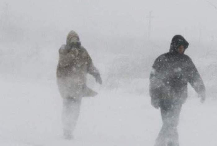 Doi oameni, îmbrăcați de iarnă, merg prin vânt și ninsori
