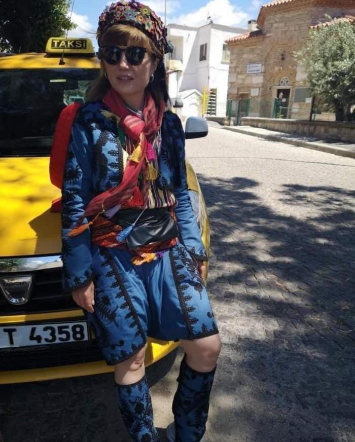 Alexandra Ungureanu, îmbrăcată în albastru, stă pe o mașină