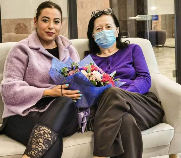Oana și Mioara Roman, pe canapea, cu flori în brațe și mască pe față