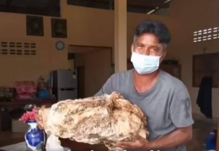 Pescarul care ține kilogramele de voă de balenă în brațe