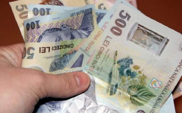 Un bărbat care ține în mână bancnote de 500 și 100 de lei
