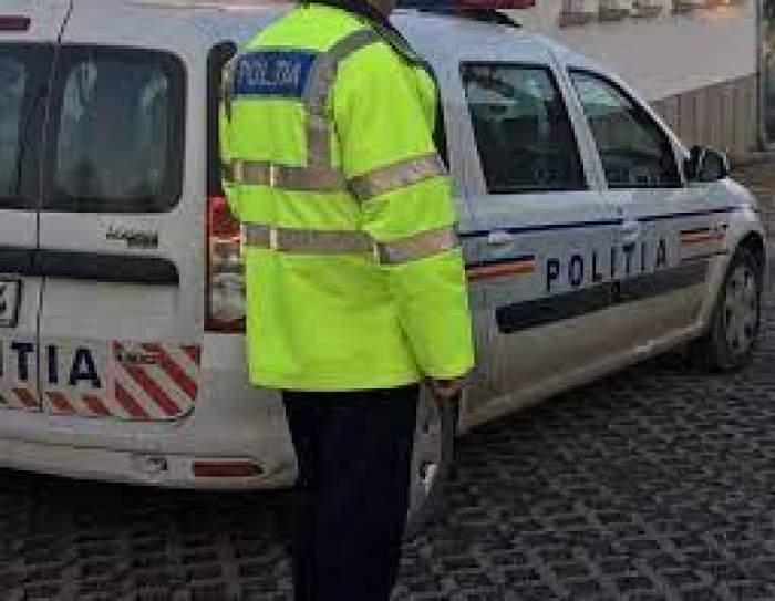 Un polițist în uniformă lângă mașina de lucru