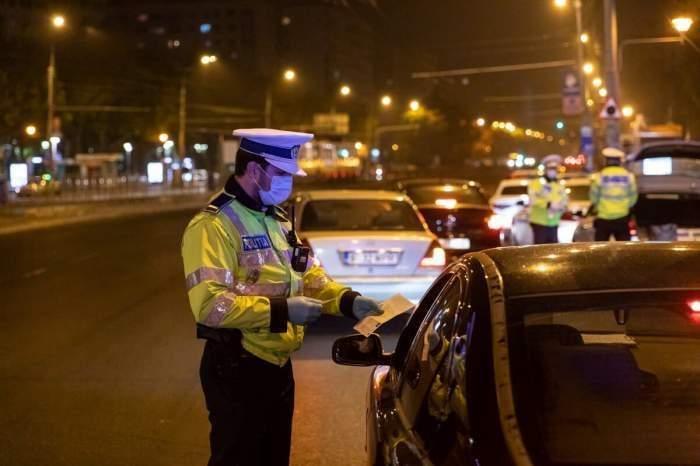 Un polițist verifică un șofer noaptea