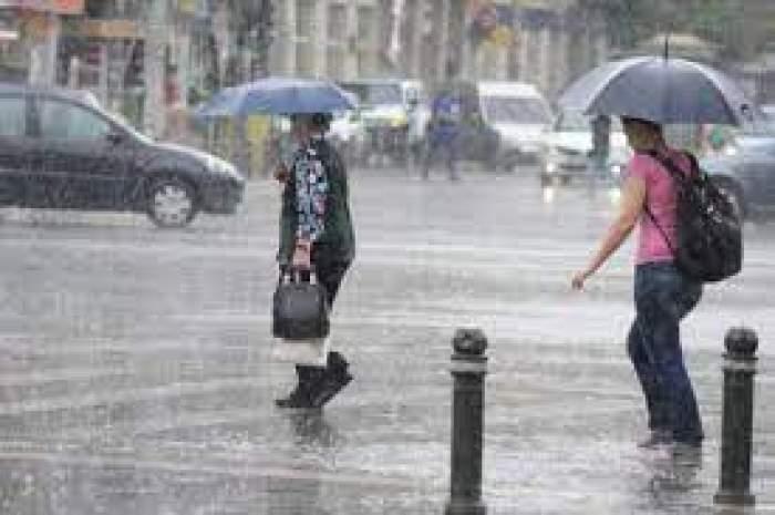 Două femei care trec strada prin ploaie