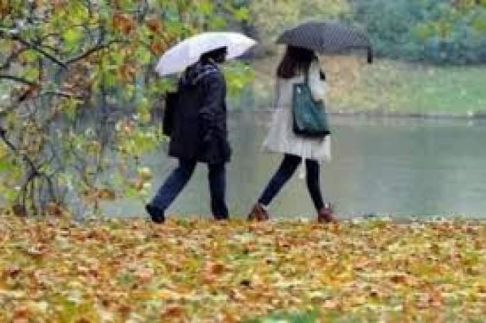 Două persoane care merg prin parc, cu umbrelele deschise