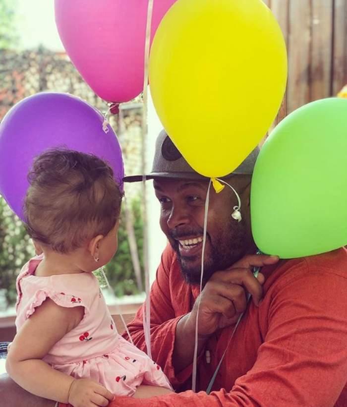 Cabral Ibacka, zâmbitor, cu fiica sa în brațe