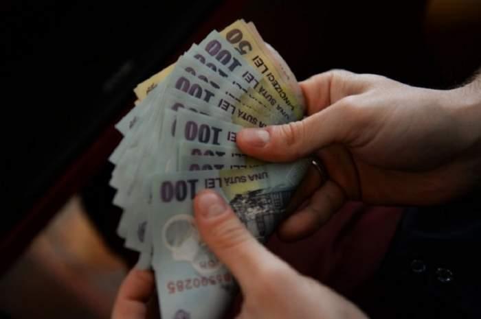 Un bărbat care ține mai multe bancnote în mână