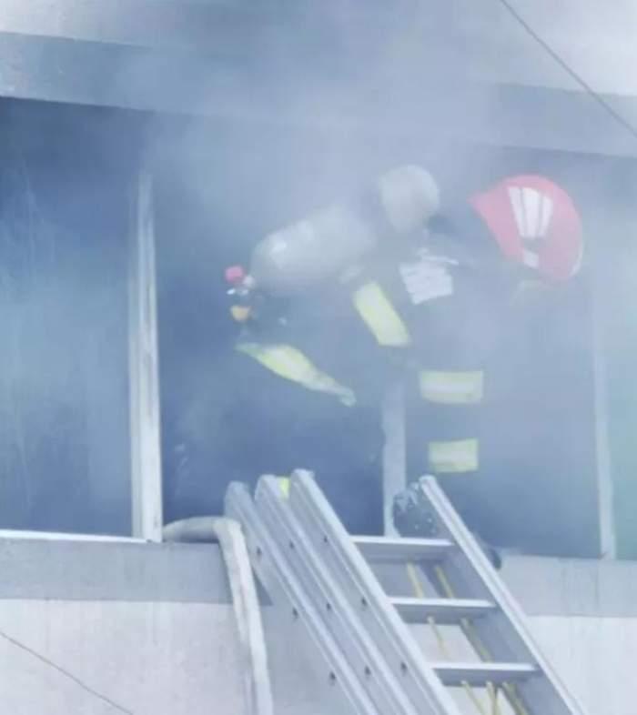 Un pompier care iese pe geam