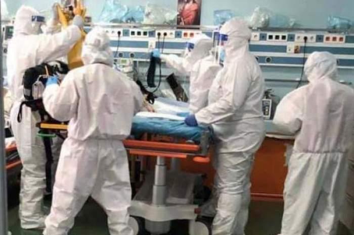 Mai mulți medici, în combinezoane, lângă un pacient