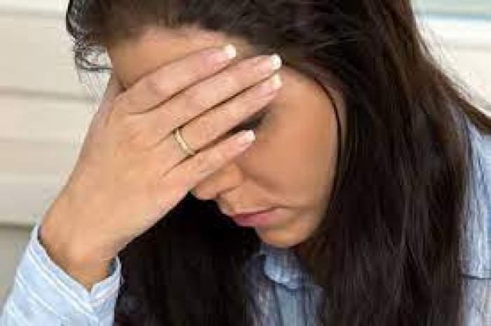 O femeie supărată cu mâna la față