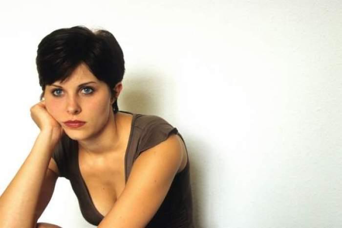 O femeie tristă, îmbrăcată în tricou negru
