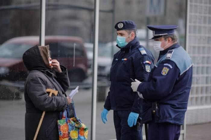 Doi polițiști care controlează o femeie în stradă