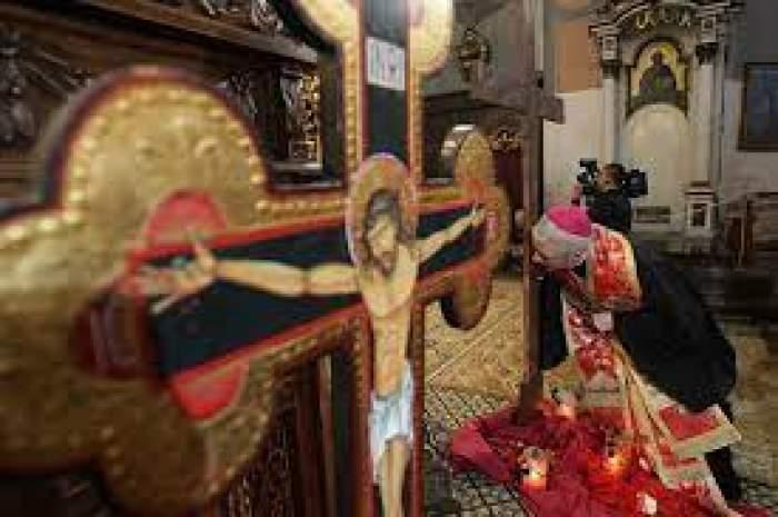 Un preot care sărută icoană și o cruce cu Iisus Hristos