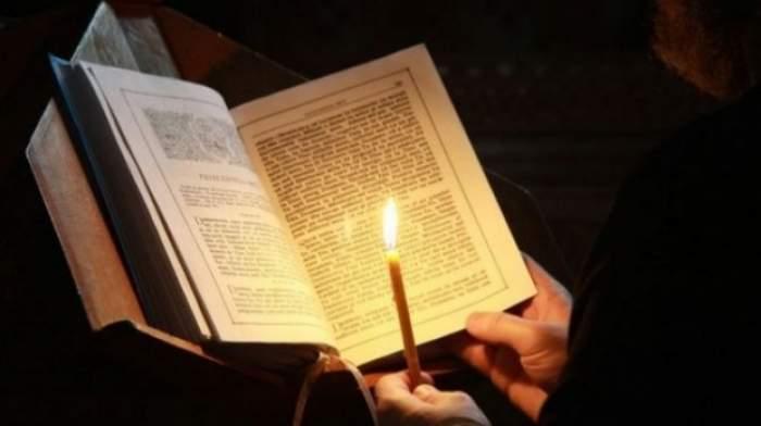 O lumânare aprinsă în dreptul unei cărți deschise