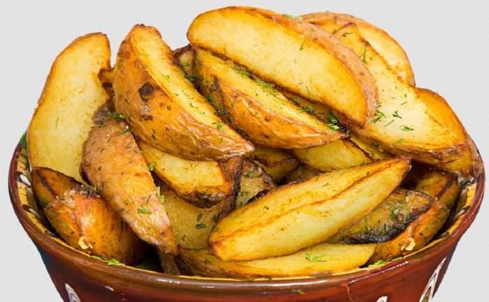 Imagine simbol cu niște cartofi tăiați felii și așezați într-un bol maro