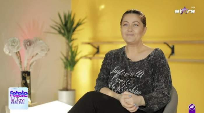Gabriela Cristea dă un interviu pentru Antena Stars. Vedeta poartă o bluză neagră și o pereche de colanți negri.