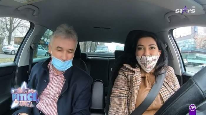 Elena Ionescu se află în mașină alături de instructorul ei auto. Cei doi partă mască de protecție. Artista poartă o rochie din piele maro, iar pe deasupra un sacou în aceleași nuanțe.