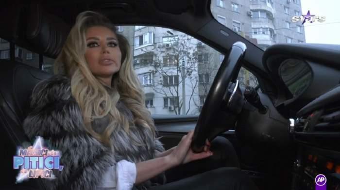 Roxana Vașniuc se află la volan. Vedeta poartă o cămașă albă, iar pe deasupra o haină de blană cenușie.