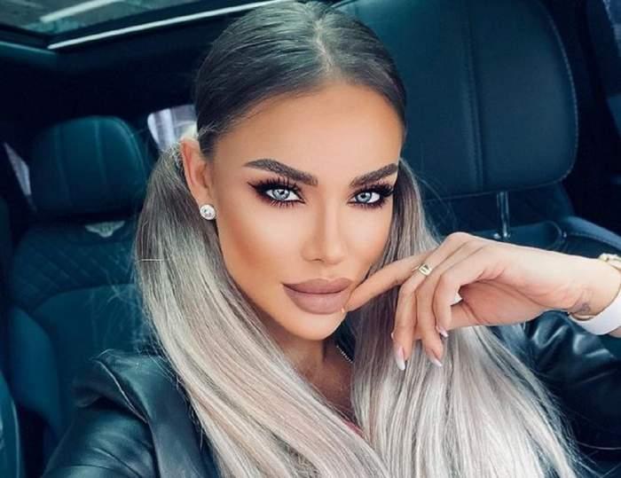 Bianca Drăgușanu se află în mașină. Vedeta are părul prins în două codițe, poartă geacă de piele și ține un deget sub bărbie.