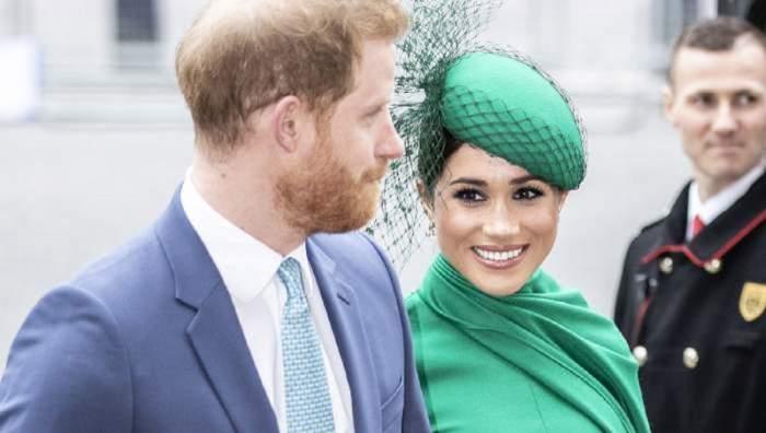 Prințul Harry și Meghan Markle se află pe stradă. Ea poartă un costum și o pălărie verde, iar el un costum bleu.