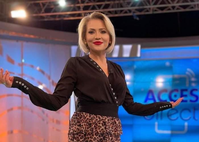 """Mirela Vaida se află în platoul """"Acces Direct"""". Vedeta poartă o cămașă neagră și o fustă scurtă cu animal print."""