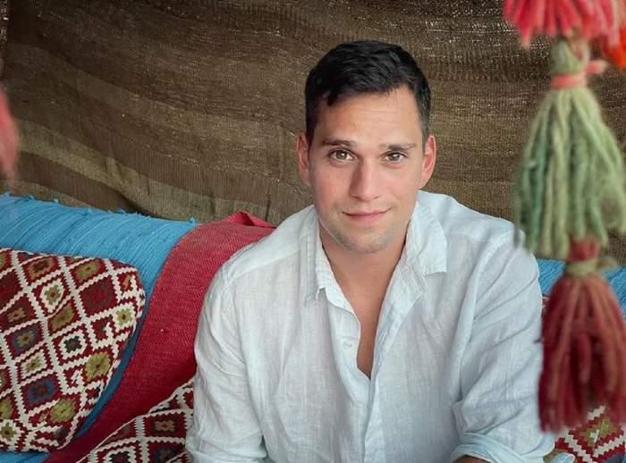 Vlad Gherman stă pe o canapea bleu. Artistul poartă o cămașă albă și zâmbește discret.