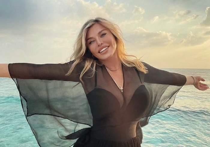 Loredana Groza poartă o rochie neagră, transparentă. Vedeta zâmbește larg și are brațele întinse.