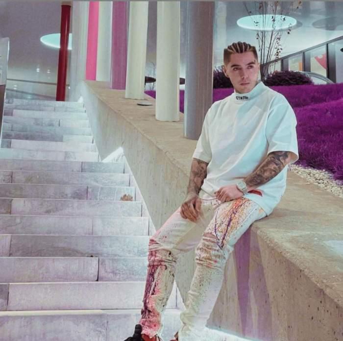 Lino Golden poarta o tinuta alba, sta pe treptele unei cladiri