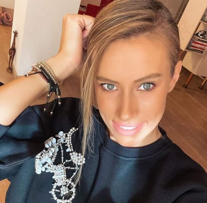 Gabriela Prisacariu are parul prins si poarta o bluza neagra cu model, zambeste si tine mana in par