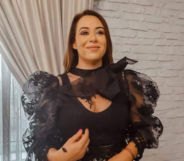Oana Roman e îmbrăcată într-o bluză neagră cu mâneci voluminoase, transparente, cu model floral. Vedeta zâmbește.