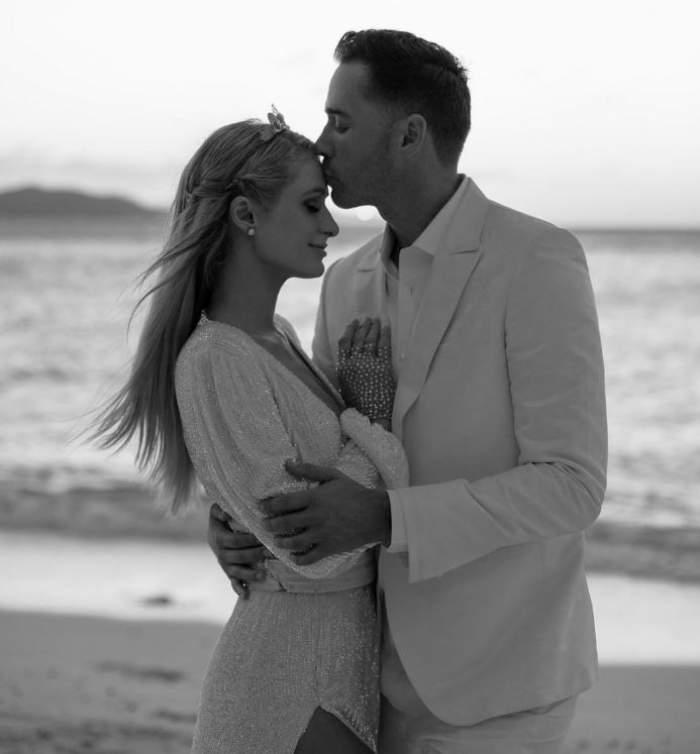 Paris Hilton si Carter Reum sunt pe plaja imbratisati, el o saruta pe frunte, ea zambeste
