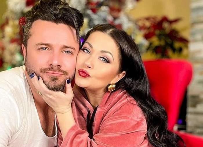 Gabriela Cristea și Tavi Clonda stau pe un fotoliu roșu. Ea poartă un trening roz, iar el tricou alb. Vedeta îl ține pe soțul ei de bărbie și are buzele țuguiate.