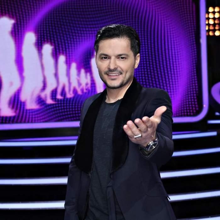 Liviu Varciu poarta un costum negru si este prezentator la o emisiune TV
