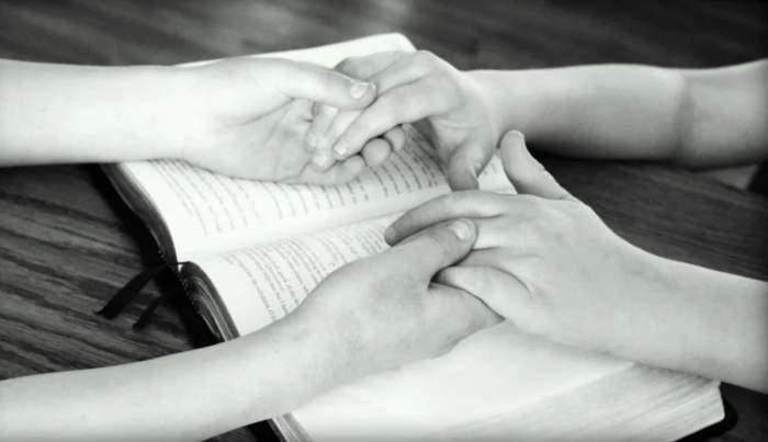 doua persoane se tin de maini si se roaga