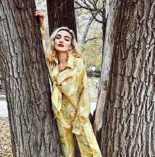 Ana Morodan e în parc, între doi copaci. Vedeta poartă un costum galben cu elemente florale verzi.
